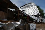 Warga merapikan rumah yang rusak akibat puting beliung di Desa Kedungrejo, Kecamatan Balerejo, Kabupaten Madiun, Jawa Timur, Rabu (15/9/2021). Puting beliung menyertai hujan di wilayah tersebut mengakibatkan sebuah rumah roboh hingga pemiliknya meninggal dunia diduga akibat kaget, puluhan rumah rusak serta puluhan pohon tumbang. Antara Jatim/Siswowidodo/zk