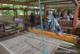USAHA TENUN SONGKET MULAI PRODUKSI DI TENGAH PANDEMI COVID-19. Perajin mengenakan masker menyelesaikan pembuatan kain songket khas Aceh  di Rumah Tenun, Desa Siem Kecamatan Darussalam Kabupaten Aceh Besar, Aceh, Rabu (15/9/2021). Kelompok perajin di Desa Siem, salah satu desa penghasil kain songket di Aceh Besar itu menyatakan, usaha tenun songket tradisional yang sempat tutup selama setahun akibat pandemi COVID-19 pada tahun 2021 mulai bangkit dan berproduksi setelah mendapat binaan dan bantuan modal usaha serta jaminan pemasaran dari BUMN. ANTARA FOTO/Ampelsa
