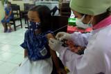 Petugas kesehatan menyuntikkan vaksin measles rubella kepada siswa SD kelas 1 saat Bulan Imunisasi Anak Sekolah (BIAS) di SD Negeri 2 Sesetan, Bali, Rabu (15/9/2021). Kegiatan imunisasi campak dan rubella tersebut menyasar 12.483 siswa SD di Denpasar untuk memutus transmisi kedua penyakit itu, menurunkan angka penderita serta menurunkan angka kejadian Congenital Rubella Syndrome (CSR). ANTARA FOTO/Nyoman Hendra Wibowo/nym.