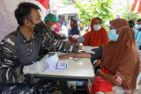Petugas kesehatan memeriksa kesehatan warga maritim saat vaksinasi COVID-19 di Posko PPKM Mikro Taman Pondok Jati, Geluran, Sidoarjo, Jawa Timur, Kamis (16/9/2021). Sekolah Tinggi Teknologi Angkatan Laut (STTAL) melakukan serbuan vaksinasi untuk mendukung kebijakan pemerintah yang menargetkan capaian pemberian 2,3 juta suntikan dosis vaksin COVID-19 per hari dan mempercepat tercapainya kekebalan kelompok (herd immunity). Antara Jaitm/Umarul Faruq/zk