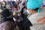 Petugas bersama orang tua membujuk anak berkebutuhan khusus agar mau divaksin saat pelaksanaan kegiatan Serbuan Vaksinasi COVID-19 di Stadion Canda Bhirawa, Kediri, Jawa Timur, Kamis (16/9/2021). Dinas Kesehatan daerah setempat menargetkan pemberian vaksin COVID-19 kepada empat ribu Orang Dengan Gangguan Jiwa (ODGJ) dan disabilitas. Antara Jatim/Prasetia Fauzani/zk