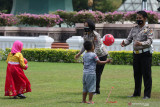 Sejumlah anak bermain bola dengan polisi saat peringatan Hari Lalulintas Bhayangkara di Tugu Pahlawan, Surabaya, Jawa Timur, Jumat (17/9/2021). Direktorat Lalu lintas (Ditlantas) Polda Jawa Timur menggelar berbagai kegiatan untuk menyambut Hari Lalulintas Bhayangkara salah satunya dengan mengadakan program pengangkatan orang tua asuh bagi anak yatim piatu terdampak COVID-19 bernama Satu Polantas Satu Anak Yatim Piatu. Antara Jatim/Didik Suhartono/zk