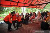 Petugas BPBD melakukan simulasi pertolongan pertama bagi korban bencana saat simulasi penanggulangan bencana di Desa Cigugur Girang, Parongpong, Lembang, Kabupaten Bandung Barat, Jawa Barat, Jumat (17/9/2021). BPBD Provinsi Jawa Barat menggelar simulasi gempa bumi bagi warga yang tinggal di kawasan sesar Lembang agar masyarakat waspada jika terjadi bencana alam. ANTARA FOTO/Raisan Al Farisi/agr