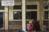 Orang tua dan siswa menunggu untuk mengambil seragam sekolah untuk persiapan Pembelajaran Tatap Muka (PTM) terbatas di SDN Anyelir 1, Depok, Jawa Barat, Jumat (17/9/2021). Pemerintah Kota Depok berencana melakukan uji coba Pembelajaran Tatap Muka (PTM) terbatas pada 20 September 2021 di SDN Anyelir 1 sebagai persiapan untuk mulai PTM terbatas pada Oktober 2021. ANTARA FOTO/Asprilla Dwi Adha/foc.
