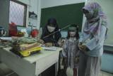 Orang tua dan siswa mengambil seragam sekolah untuk persiapan Pembelajaran Tatap Muka (PTM) terbatas di SDN Anyelir 1, Depok, Jawa Barat, Jumat (17/9/2021). Pemerintah Kota Depok berencana melakukan uji coba Pembelajaran Tatap Muka (PTM) terbatas pada 20 September 2021 di SDN Anyelir 1 sebagai persiapan untuk mulai PTM terbatas pada Oktober 2021. ANTARA FOTO/Asprilla Dwi Adha/foc.