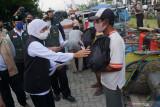 Gubernur Jawa Timur Khofifah Indar Parawansa (kiri) menyerahkan bantuan sembako kepada warga pengayuh becak di sela kegiatannya meninjau pelaksanaan vaksinasi COVID-19 yang digelar Ikatan Sarjana Nahdlatu Ulama (ISNU) di Universitas Islam Negeri Sayyid Ali Rahmatullah Tulungagung (UIN SATU), Tulungagung, Jawa Timur, Sabtu (18/9/2021). Antara Jatim/Destyan Sujarwoko/zk