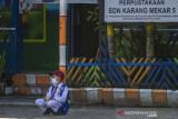 Seorang siswa menunggu orang tuanya di SD Negeri Karang Mekar 5, Banjarmasin, Kalimantan Selatan, Senin (20/9/2021). Pemerintah Kota Banjarmasin melalui Dinas Pendidikan Kota Banjarmasin kembali melaksanakan Pembelajaran Tatap Muka (PTM) untuk semua jenjang pendidikan yakni Pendidikan Anak Usia Dini (PAUD), Sekolah Dasar (SD) dan Sekolah Menengah Pertama (SMP) setelah mendapat izin atau rekomendasi dari Satgas COVID-19 Banjarmasin Serta mempertimbangkan Surat Keputusan Bersama (SKB) empat Menteri dengan penerapan disiplin protokol kesehatan yang ketat. Foto Antaranews Kalsel/Bayu Pratama S.