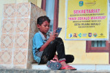 Seorang bocah menggunakan telepon genggam untuk menikmati akses internet gratis di Kantor Desa Muara Sekalo, penyangga Taman Nasional Bukit Tigapuluh (TNBT), Sumay, Tebo, Jambi, Minggu (19/9/2021). Layanan internet yang terhubung secara nirkabel di desa yang berbatasan langsung dengan TNBT dan memiliki kendala sinyal jaringan seluler tersebut diberikan untuk membantu kebutuhan akses internet warga. ANTARA FOTO/Wahdi Septiawan/aww.