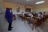 Siswa kelas XII SMK PGRI 3 Denpasar mengikuti pelajaran Bahasa Inggris saat Pembelajaran Tatap Muka (PTM) di Denpasar, Bali, Senin (20/9/2021). PTM yang digelar perdana di sekolah tersebut menerapkan protokol kesehatan dan mengatur jumlah siswa 50 persen di setiap kelas dengan dibagi menjadi dua sesi yakni sesi pertama dimulai pukul 08.00 - 10.00 WITA dan sesi kedua dimulai pukul 10.30 - 12.30 WITA serta sudah mendapat persetujuan dari orang tua siswa. ANTARA FOTO/Nyoman Hendra Wibowo/nym.