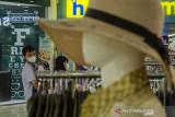 Pengunjung mengendong anaknya saat berkunjung ke pusat perbelanjaan Bandung Indah Plaza, Bandung, Jawa Barat, Selasa (21/9/2021). Pemerintah Indonesia kembali menerapkan penyesuaian PPKM level 3 dan level 2 pandemi COVID-19 dengan memperbolehkan anak di bawah usia 12 tahun untuk masuk mal dengan pendampingan orang tua dan penerapan protokol kesehatan yang ketat. ANTARA FOTO/Novrian Arbi/agr