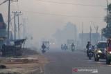 Sejumlah pengendara motor melintas di jalan yang diselimuti kabut asap kebakaran lahan di Kecamatan Liang Anggang, Banjarbaru, Kalimantan Selatan, Selasa (21/9/2021). Kencangnya angin di lokasi yang terbakar membuat api dengan cepat membakar lahan yang diperkirakan mencapai puluhan hektare hingga kini BPBD Kota Banjarbaru dibantu relawan pemadam kebakaran Kota Banjarmasin berupaya memadamkan api yang mendekati permukiman penduduk di daerah setempat. Foto Antaranews Kalsel/Bayu Pratama S.