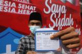 Seorang santri memperlihatkan kartu vaksinasi usai mendapatkan suntikan vaksin COVID-19 di Pondok Pesantren Al Ihsan Jampes, Kediri, Jawa Timur, Selasa (21/9/2021). Sebanyak 80 persen santri dari jumlah total 20 ribu santri berusia 12 tahun ke atas di Kediri telah mendapatkan suntikan vaksin COVID-19. Antara Jatim/Prasetia Fauzani/zk
