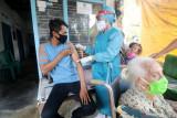 Petugas medis menyuntikkan vaksin COVID-19 di depan rumahnya di Desa Turus, Kediri, Jawa Timur, Selasa (21/9/2021). Layanan vaksinasi COVID-19 dari rumah ke rumah tersebut guna memudahkan masyarakat berusia 12 tahun ke atas mendapatkan vaksin sebagai upaya mempercepat kekebalan komunal. Antara Jatim/Prasetia Fauzani/zk
