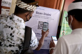Warga memindai kode Quick Response (QR) dengan aplikasi PeduliLindungi sebelum memasuki Mal Pelayanan Publik di Denpasar, Bali, Selasa (21/9/2021). Seluruh pegawai serta masyarakat yang akan mengurus administrasi dan layanan publik lainnya di Mal Pelayanan Publik tersebut diwajibkan untuk menggunakan aplikasi PeduliLindungi sebagai upaya pencegahan penyebaran COVID-19. ANTARA FOTO/Fikri Yusuf/nym.