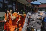 Anggota kepolisian menggiring tersangka saat rilis pengungkapan industri rumahan pengolahan narkoba di Polres Bogor, Kabupaten Bogor, Jawa Barat, Selasa (21/9/2021). Satuan Reserse Narkoba Polres Bogor bersama Ditresnarkoba Polda Jawa Barat berhasil mengamankan barang bukti sebanyak 23,45 kg bahan baku (biang) tembakau sintetis dan 2,7 kg tembakau sintetis siap edar serta berbagai alat pengolahan dari 11 tersangka. ANTARA FOTO/Yulius Satria Wijaya/wsj.