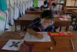 Siswa SD Negeri 3 Batubulan mengikuti pembelajaran tatap muka (PTM) dengan menerapkan protokol kesehatan di Gianyar, Bali, Rabu (22/9/2021). Satuan pendidikan di Bali diizinkan melaksanakan PTM terbatas dan wajib berkoordinasi dengan Satgas COVID-19 setempat sesuai Surat Edaran Gubernur Bali dengan nomor B.31.420/76560/DIKPORA tentang pelaksanaan pembelajaran pada masa pandemi COVID-19 di Provinsi Bali. ANTARA FOTO/Nyoman Hendra Wibowo/nym.