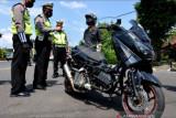 Polisi menegur pengendara sepeda motor yang tidak sesuai dengan standar saat pelaksanaan Operasi Patuh Agung 2021 di Badung, Bali, Rabu (22/9/2021). Operasi Patuh Agung 2021 di wilayah Bali dilaksanakan hingga 3 Oktober mendatang untuk meningkatkan keamanan, keselamatan dan ketertiban masyarakat dalam berlalu lintas serta meningkatkan kedisiplinan penerapan protokol kesehatan guna mencegah penyebaran COVID-19. ANTARA FOTO/Fikri Yusuf/nym.