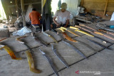 PERAJIN RENCONG TERDAMPAK PANDEMI. Perajin menyelesaikan pembuatan senjata tradisional Rencong Aceh di rumah produksi pandai besi, desa Baet Masjid, kecamatan Suka Makmur, Kabupaten Aceh Besar, Aceh, Rabu (22/9/2021). Menurut perajin, selama pandemi COVID-19 permintaan senjata tradisional Rencong Aceh menurun dan hanya di produksi jika ada permintaan masyarakat sebagai cenderamata souvenir dengan harga penjualan Rp 150.000 hingga Rp450.000 per rencong menurut jenis,ukuran serta bahan bakunya. ANTARA FOTO/Ampelsa.