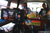 Penyiar mewancarai seorang narasumber di sebuah angkutan kota yang diubah menjadi studio siniar (podcast) keliling di Malang, Jawa Timur, Rabu (22/9/2021). Studio podcast keliling dari angkutan tersebut dioperasikan untuk mempromosikan keunikan kawasan wisata setempat dalam upaya pemulihan ekonomi wisata. Antara Jatim/Ari Bowo Sucipto/zk