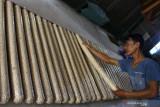 Pekerja menata tempe yang dibuat dari kedelai impor di sentra industri tempe di Sanan, Malang, Jawa Timur, Kamis (23/9/2021). Fluktuasi harga kedelai impor yang tergolong tinggi yakni berada di kisaran Rp9.700 per kilogram membuat perajin tempe setempat memperkecil ukuran tempe serta menaikkan harga dari Rp1.500 menjadi 2.000 rupiah per bungkus untuk mengatasi pembengkakan biaya produksi dalam enam bulan terakhir. Antara Jatim/Ari Bowo Sucipto/zk