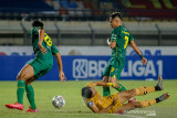 Pesepakbola Bhayangkara FC Dendy Sulistyawan (tengah) terjatuh saat berduel dengan pesepakbola Persebaya Surabaya Reva Adi Utama (kanan) saat berlaga pada BRI Liga 1 di Stadion Si Jalak Harupat, Kabupaten Bandung, Jawa Barat, Jumat (24/9/2021). Pertandingan tersebut dimenangkan oleh Bhayangkara FC dengan skor 0-1. ANTARA FOTO/Raisan Al Farisi/agr