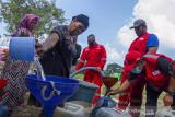 Petugas gabungan dari Palang Merah Indonesia (PMI) mengisi air bersih saat pendistribusian air secara gratis di Desa Kertasari, Pangkalan, Karawang, Jawa Barat, Sabtu (25/9/2021). PMI bersama Tagana mendistribusikan sebanyak 31 ribu liter air bersih untuk warga yang mengalami kesulitan air bersih sebanyak 595 Kartu Keluarga (KK). ANTARA FOTO/M Ibnu Chazar/agr