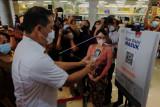 Menteri Perdagangan Muhammad Lutfi (kiri) melakukan pemindaian kode batang sertifikat vaksin COVID-19 melalui aplikasi PeduliLindungi saat kunjungan kerja di swalayan Tiara Dewata, Denpasar, Bali, Sabtu (25/9/2021). Kunjungan Menteri Perdagangan di swalayan tersebut meninjau kesiapan untuk pembukaan dan penerapan SOP PeduliLindungi pada supermarket dan departement store di luar mal sebagai upaya pencegahan penyebaran COVID-19. ANTARA FOTO/Nyoman Hendra Wibowo/nym.