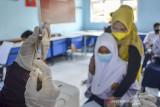 Petugas kesehatan menyiapkan vaksin COVID-19 di Ruang Kelas SMP Negeri 2 Ciamis, Kabupaten Ciamis, Jawa Barat, Sabtu (25/9/2021). Sebanyak 3.196 pelajar SMP mengikuti gebyar vaksinasi anak dosis kedua yang digelar di tujuh sekolah di Ciamis, untuk mempercepat terbentuknya herd immunity atau kekebalan komunal saat pelaksanaan Pembelajaran Tatap Muka (PTM) terbatas. ANTARA FOTO/Adeng Bustomi/agr