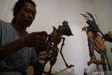 Perajin Joko menyelesaikan pembuatan kerajinan wayang berbahan kayu di Mojorejo, Kebonsari, Kabupaten Madiun, Jawa Timur, Minggu (26/9/2021). Hasil kerajinan tersebut dijual dengan harga antara Rp350 ribu hingga Rp5 juta per buah. Antara Jatim/Siswowidodo/zk