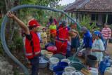 Petugas gabungan dari Palang Merah Indonesia (PMI) bersama Taruna Siaga Bencana (Tagana) mendistribusikan air gratis di Desa Kertasari, Pangkalan, Karawang, Jawa Barat, Sabtu (25/9/2021). PMI bersama Tagana mendistribusikan sebanyak 31 ribu liter air bersih untuk warga yang mengalami kesulitan air bersih sebanyak 595 Kartu Keluarga (KK). ANTARA FOTO/M Ibnu Chazar/rwa.