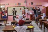 Komunitas Badut Tasikmalaya (Battik) menyanyikan lagu 3M saat sosialisasi protokol kesehatan pada pembelajaran tatap muka SD Negeri Dadaha, Kota Tasikmalaya, Jawa Barat, Senin (27/9/2021). Komunitas Badut Tasikmalaya melakukan edukasi protokol kesehatan dengan aktraksi dan permainan interaktif serta membagikan masker guna mencegah penyebaran COVID-19 serta meminimalisasi klaster baru di lingkungan sekolah saat pembelajaran tatap muka terbatas. ANTARA FOTO/Adeng Bustomi/agr