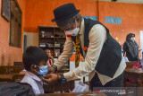Komunitas Badut Tasikmalaya (Battik) mengenakan masker ke siswa saat sosialisasi protokol kesehatan pada pembelajaran tatap muka SD Negeri Dadaha, Kota Tasikmalaya, Jawa Barat, Senin (27/9/2021). Komunitas Badut Tasikmalaya melakukan edukasi protokol kesehatan dengan aktraksi dan permainan interaktif serta membagikan masker guna mencegah penyebaran COVID-19 serta meminimalisasi klaster baru di lingkungan sekolah saat pembelajaran tatap muka terbatas. ANTARA FOTO/Adeng Bustomi/agr