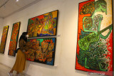 Pengunjung melihat lukisan berjudul Etnik Nusantara V karya seniman Amdo Brada yang dipajang dalam pameran seni bertajuk  Spirit From The East#2 di Gedung Dewan Kesenian Malang, Jawa Timur, Senin (27/9/2021). Pameran yang mengusung tema keanekaragaman budaya dan kesenian nusantara tersebut berlangsung selama delapan hari dengan menampilkan 50 karya dari sebelas seniman dari Malang, Surabaya, Batu dan Tulungagung. Antara Jatim/Ari Bowo Sucipto/zk.