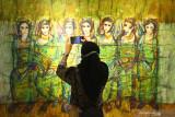 Pengunjung memotret lukisan berjudul Bidadari Menunggu karya seniman Anthony Wibowo yang dipajang dalam pameran seni bertajuk  Spirit From The East#2 di Gedung Dewan Kesenian Malang, Jawa Timur, Senin  (27/9/2021). Pameran yang mengusung tema keanekaragaman budaya dan kesenian nusantara tersebut berlangsung selama delapan hari dengan menampilkan 50 karya dari sebelas seniman dari Malang, Surabaya, Batu dan Tulungagung. Antara Jatim/Ari Bowo Sucipto/zk.