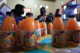 Pekerja menyelesaikan pembuatan jus mangga di desa Kenanga, Indramayu, Jawa Barat, Selasa (28/9/2021). Jus mangga yang diproduksi oleh Desmigratif (Desa Migran Produktif) Kenanga Mandiri tersebut dijual seharga Rp8.000 per botol dan dipasarkan ke berbagai daerah melalui media daring. ANTARA FOTO/Dedhez Anggara/agr