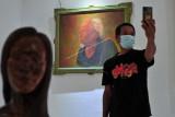 Pengunjung berfoto dengan latar belakang lukisan