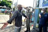 Warga yang terjaring sidak protokol kesehatan karena tidak mengenakan masker dengan benar berdebat dengan petugas di Denpasar, Bali, Selasa (28/9/2021). Sidak tersebut terus dilakukan petugas gabungan selama PPKM Level 3 di wilayah Denpasar untuk memastikan penerapan protokol kesehatan oleh masyarakat khususnya kesadaran penggunaan masker yang terpantau menurun dengan meningkatnya jumlah warga yang terjaring razia pada beberapa hari terakhir. ANTARA FOTO/Fikri Yusuf/nym.