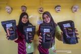 Puteri Pariwisata Kabupaten Hulu Sungai Tengah Kalsel menunjukkan tiga jenis kopi saat launching Kopi Meratus di obyek wisata Pagat, Barabai, Kabupaten Hulu Sungai Tengah, Kalimantan Selatan, Jumat (1/10/2021). Dalam mewujudkan pertumbuhan dan pengembangan ekonomi yang ramah lingkungan berbasis kerakyatan, Serikat Petani Indonesia (SPI) Kalimantan Selatan bersama Pemerintah Daerah Hulu Sungai Tengah meluncurkan Kopi Meratus dengan tiga jenis kopi yaitu kopi Robusta, Liberika dan Ekselsa yang tumbuh di Pegunungan Meratus sekaligus dalam rangka memperingati Hari Kopi Dunia 2021 (International Coffee Day). Foto Antaranews Kalsel/Bayu Pratama S.
