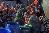 Sesepuh warga menyiramkan air kepada sejumlah warga lainnya saat menjgikuti tradisi mandi tolak bala Rebo Wekasan di Kampung Karundang, Serang, Banten, Rabu (6/10/2021). Tradisi tersebut berlangsung pada hari Rabu setiap akhir bulan Shafar pada penanggalan Jawa untuk memohon perlindungan dari segala macam bencana. ANTARA FOTO/Asep Fathulrahman/nym.