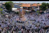 Ratusan warga mengiringi arak-arakan bade atau menara usungan jenazah Ida Pedanda Nabe Gede Dwija Ngenjung saat upacara Ngaben di kawasan Sanur, Denpasar, Bali, Jumat (8/10/2021). Upacara Ngaben mendiang pemuka agama Hindu sekaligus tokoh pariwisata tersebut merupakan upacara berskala besar pertama yang digelar selama masa pandemi COVID-19 setelah turunnya level PPKM di Bali dari level 4 berubah menjadi level 3. ANTARA FOTO/Nyoman Hendra Wibowo/nym.