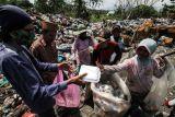 Warga membagikan nasi kotak kepada pemulung di Tempat Pembuangan Akhir (TPA) Alue Lim Lhokseumawe, Aceh, Jumat (8/10/2021). Pembagian makanan gratis tersebut untuk membantu meringankan beban ekonomi masyarakat sebagai bentuk kepedulian terhadap sesama di tengah pandemi COVID-19. ANTARA FOTO/Rahmad/rwa.