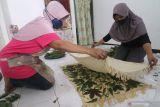 Perajin menutup tatanan daun menggunakan kain katun saat proses pembuatan sajadah ecoprint di Cabhi Craft, Desa Paron, Kediri, Jawa Timur, Minggu (10/10/2021). Kerajinan sajadah dengan pewarnaan alami tersebut dipasarkan melalui media sosial seharga Rp100 ribu per lembar. Antara Jatim/Prasetia Fauzani/zk.