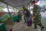 Anggota TNI membantu warga menuju meja penerima bantuan tunai PKL dan Warung (BTPKLW) di Makodim 1007 Banjarmasin, Kalimantan Selatan, Rabu (13/10/2021). Mabes TNI melalui Kodim 1007 Banjarmasin menyalurkan BPTPKLW yang merupakan program pemerintah kepada 3.200 pedagang kaki lima dan pemilik warung sebesar Rp1,2 juta untuk setiap penerima guna membantu mereka bertahan dan memulihkan usaha akibat terdampak pandemi COVID-19. Foto Antaranews Kalsel/Bayu Pratama S.
