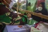 Prajurit TNI membantu warga untuk mengisi data penerima bantuan tunai PKL dan Warung (BTPKLW) di Makodim 1007 Banjarmasin, Kalimantan Selatan, Rabu (13/10/2021). Mabes TNI melalui Kodim 1007 Banjarmasin menyalurkan BPTPKLW yang merupakan program pemerintah kepada 3.200 pedagang kaki lima dan pemilik warung sebesar Rp1,2 juta untuk setiap penerima guna membantu mereka bertahan dan memulihkan usaha akibat terdampak pandemi COVID-19. Foto Antaranews Kalsel/Bayu Pratama S.
