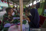Anggota TNI membantu warga untuk mengisi data penerima bantuan tunai PKL dan Warung (BTPKLW) di Makodim 1007 Banjarmasin, Kalimantan Selatan, Rabu (13/10/2021). Mabes TNI melalui Kodim 1007 Banjarmasin menyalurkan BPTPKLW yang merupakan program pemerintah kepada 3.200 pedagang kaki lima dan pemilik warung sebesar Rp1,2 juta untuk setiap penerima guna membantu mereka bertahan dan memulihkan usaha akibat terdampak pandemi COVID-19. Foto Antaranews Kalsel/Bayu Pratama S.
