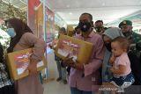 VAKSINASI DAN BANSOS AKABRI 89 DI ACEH. Penyandang disabilitas membawa paket bantuan sosial saat berlangsung vaksinasi COVID-19 pada kegiatan Pengabdian 33 tahun TNI-Polri AKABRI 89 di Lapangan Blang Padang, Banda Aceh, Aceh, Rabu (13/10/2021). Kegitan pengabdian 33 tahun TNI-Polri AKABRI 89 dalam rangka HUT ke 76 TNI yang berlangsung serentak di sejumlah provinsi, termasuk di Aceh  tersebut menggelar kegiatan vaksinasi dalam rangka percepatan penangganan COVID-19 dan penyaluran bantuan sosial untuk warga kurang mampu. ANTARA FOTO/Ampelsa.