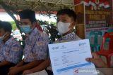 VAKSINASI DAN BANSOS AKABRI 89 DI ACEH. Pelajar memperlihatkan kartu vaksinasi COVID-19 seusai disuntuk vaksin saat berlangsung kegiatan Pengabdian 33 tahun TNI-Polri AKABRI 89 di Lapangan Blang Padang, Banda Aceh, Aceh, Rabu (13/10/2021). Kegitan pengabdian 33 tahun TNI-Polri AKABRI 89 dalam rangka HUT ke 76 TNI yang berlangsung serentak di sejumlah provinsi, termasuk di Aceh  tersebut menggelar kegiatan vaksinasi dalam rangka percepatan penangganan COVID-19 dan penyaluran bantuan sosial untuk warga kurang mampu. ANTARA FOTO/Ampelsa.