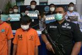 Petugas BNN Provinsi Bali memperlihatkan barang bukti sabu-sabu dan tersangka mahasiswa berinisial MS (kiri) saat konferensi pers hasil pengungkapan kasus tindak narkotika di kantor BNN Provinsi Bali, Denpasar, Bali, Rabu (13/10/2021). Mahasiswa asal Lampung yang menjadi penerima narkotika jenis sabu-sabu tersebut ditangkap oleh petugas tim opsnal BNN Provinsi Bali di sebuah penginapan di kawasan Renon, Denpasar pada Rabu (6/10/2021) dengan barang bukti 10 buah plastik klip berisi sabu-sabu dengan berat keseluruhan 1 kg. ANTARA FOTO/Nyoman Hendra Wibowo/nym.