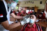 Petugas kesehatan melakukan tes 'swab' antigen COVID-19 secara acak kepada siswa SMP Negeri 3 Abiansemal di Badung, Bali, Rabu (13/10/2021). Pemerintah Kabupaten Badung melakukan tes COVID-19 antigen secara acak bagi pelajar sejumlah sekolah untuk memastikan kesehatan siswa dan mencegah terjadinya klaster penyebaran COVID-19 di sekolah selama Pembelajaran Tatap Muka (PTM) terbatas. ANTARA FOTO/Fikri Yusuf/nym.