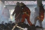 Petugas Dinas Pemadam Kebakaran Kota Surabaya melakukan pembasahan ruangan yang terbakar di komplek Kantor Kementerian Pekerjaan Umum dan Perumahan Rakyat Jalan Gayung Kebonsari No 50, Surabaya, Jawa Timur, Rabu (13/10/2021). Sebanyak 14 unit kendaraan pemadam kebakaran dikerahkan untuk memadamkan api yang membakar satu ruang kantor dan sejumlah ruangan penyimpanan dokumen tersebut. Antara Jatim/Didik Suhartono/zk.